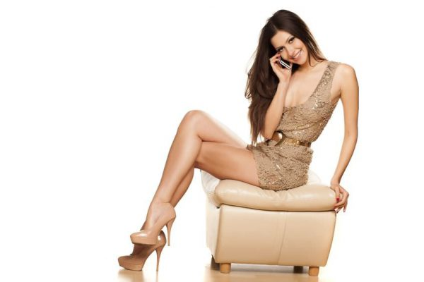 セクシーなブルネットの座っている笑顔とショート ドレスで電話をかけ
