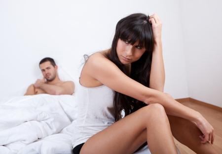 けんかを自宅で若いカップル。ベッドに座っています。